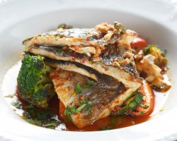 Oven cooked sea bass with small vegetables and capers image