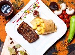 Coaste de porc cu sos BBQ servit cu cartofi prăjiți image