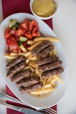Platou mici sârbești cu salată asortată, cartofi prăjiți și muștar image