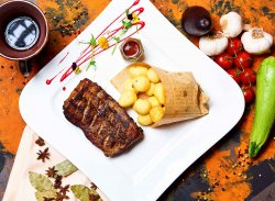 Coaste de porc cu sos BBQ servit cu cartofi prajiți