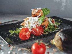 Melanzana con formaggio di pecora e miele su un lettino di rucola e pomodorini al forno