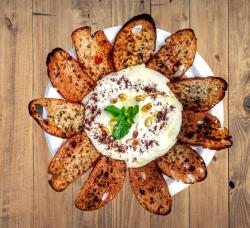 Humus cu muguri de pin și sumac, servit cu pâine integrală de casă, dată la cuptor cu mirodenii image