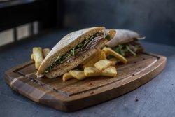 Porchetta sandwich served with fries