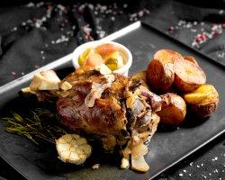 Stinco di maiale con patate dorate, aglio e giardiniera