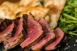 Tagliata din antricot de vită la grătar cu dresing chimichurri pe salată de rucola/Grilled beef Tagliata steak with Chimichurri dressing with rocket salad