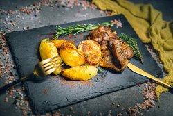 Pulpă coaptă la tavă cu cartofi condimentați și rumeniți image